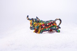 Bull of colored mosaic on fluffy snow