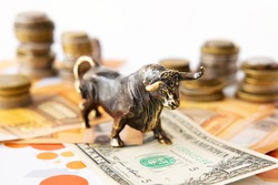 Bull standing on one dollar banknote with stacks of coins behind