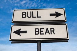 Bull vs bear. White two street signs with arrow on metal pole with word. Directional road. Crossroads Road Sign, Two Arrow. Blue sky background. Two way road sign with text.