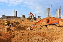 Bulldozer and excavator for earthworks  at construction site. Earth-moving equipment for land clearing, grading and utility trenching and foundation digging. Dozer and backhoe digging the ground
