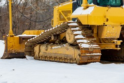 Bulldozer at construction site after winter snow storm. Concept of construction industry, work delay and stoppage.