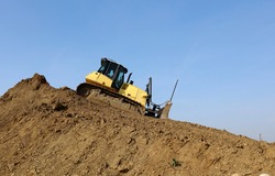 Bulldozer at work on the descent of a large pile of dirt. Side view.