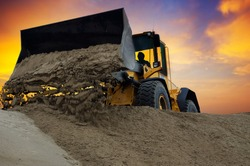 Bulldozer at work with sunset background