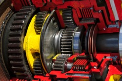 Bulldozer drive gear mechanism cross section, sprockets, bearings of diesel engine, large construction machine of red and yellow colors, heavy industry