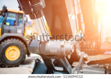 Bulldozer, focus on hydraulic piston shoulder, heavy industry, tractor yellow. new technology at the exhibition