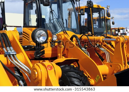 Bulldozer headlight, row of huge orange powerful construction machines, tractors, excavators, focused on spotlight, blue sky and white clouds on background, selective focus