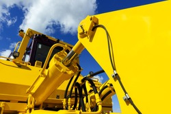 Bulldozer, huge yellow powerful construction machinery with big bucket, focused on hydraulic piston arm, blue sky and white clouds on background