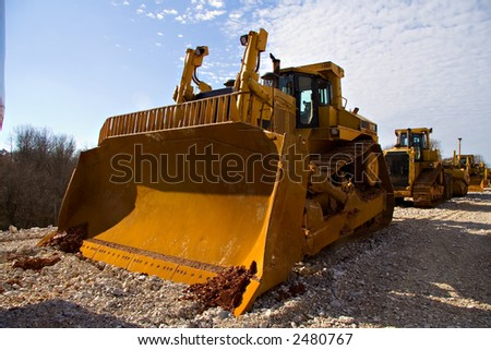 Bulldozer in long line of heavy equipment