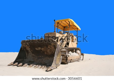 bulldozer in the sand with blue background