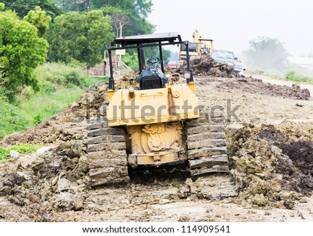 Bulldozer machine doing earth moving work in construction site - stock photo