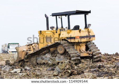 Bulldozer machine doing earth moving work in construction site