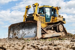 Bulldozer machine is leveling construction site. Earthmover with caterpillar is moving earth. Close-up. Construction heavy machinery