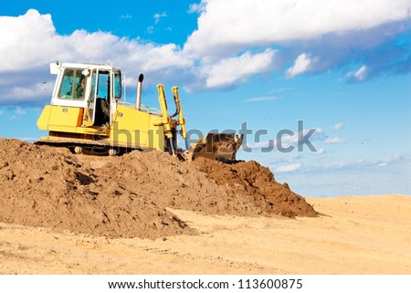 Bulldozer machine moving soil at construction site during earth moving works