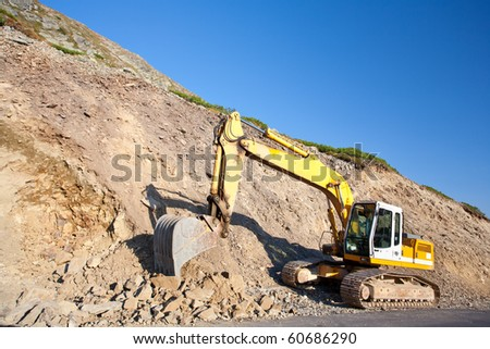 Bulldozer or excavator, industrial machinery against the blue sky