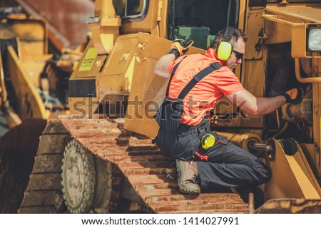 Bulldozer Professional Mechanic. Caucasian Technician Taking Machine Under Maintenance. Construction Heavy Duty Equipment. #1414027991