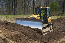 Bulldozer pushing dirt on construction site near a big airport