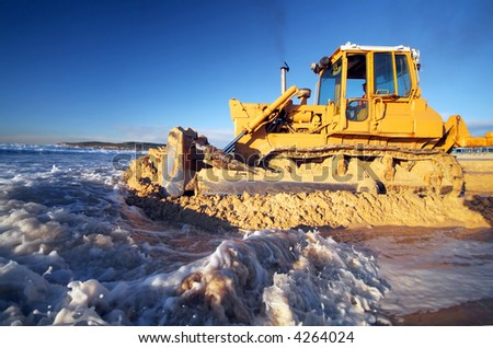 Bulldozer pushing excess sand off beach after big storm surge
