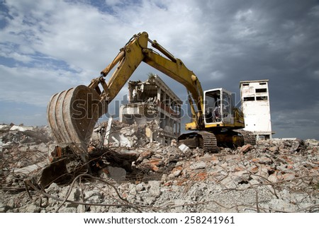 Bulldozer Removes the Debris From Demolition of Old Derelict Buildings