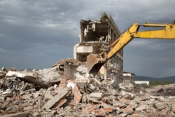 Bulldozer Removes the Debris From Demolition of Old Derelict Buildings on the Construction Site