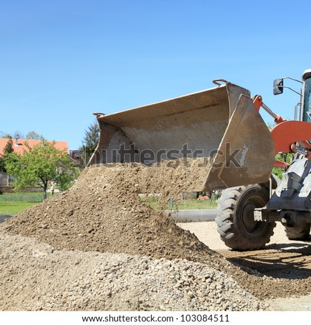 Bulldozer  taking gravel and sand to bucket