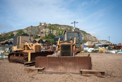 Bulldozer tracked vehicles, and tractors on the beach at Hastings, used to tug and pull boats from the sea onto the beach. Hastings, Kent, UK