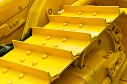 Bulldozer tracks and drive gear with sprocket mechanism, large construction machine with bolts and yellow paint coating, heavy industry, detail