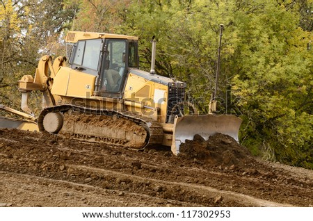 Bulldozer tractor works at moving soil and rock for a new commercial housing development.