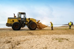 Bulldozers clean up trash on the beach