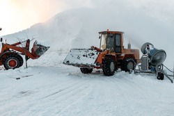 Bulldozers remove the snow that the snow cannons have made.