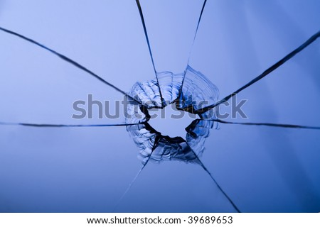 bullet hole in glass on blue with crack