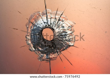 bullet hole in window on the background sunset sky