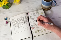 Bullet journal open on self care healthy habits layout pages with hand holding pen. Over shoulder view, fresh white table background, flowers, positive mental health message.