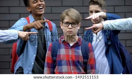 Bullied boy looking at camera, depressed by classmates mockery, verbal abuse