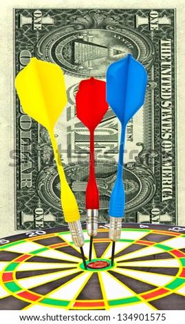 Bulls eye with dollar bill pinned by 3 darts, close up on one bill dollar