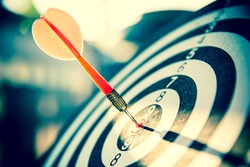 Bullseye(bull's-eye) or dart board has dart arrow hitting the center of a shooting target for business targeting and good success.