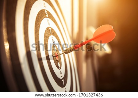Bullseye(bull's-eye) or dart board has dart arrow hitting the center of a shooting target for business targeting and and  marketing goal concetps.