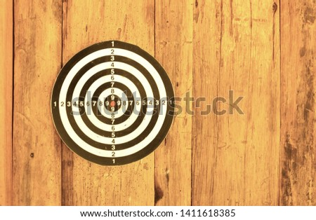 Bullseye is a target of business. Dart is an opportunity and Dartboard on old wood background. #1411618385
