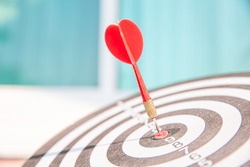 Bullseye or dart board has dart arrow throw hitting the center of a shooting target with sunshine for business targeting and winning goals business concepts.