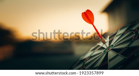 bullseye target or dart board has red dart arrow throw hitting the center of a shooting for business targeting and winning goals business concepts. Stock photo ©