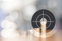 BULLSEYE TARGET RIGHT AT THE HIGHEST STACKED US QUARTER COINS WITH NICE BOKEH OF LIGHT AND COPY SPACE / FINANCIAL CONCEPT