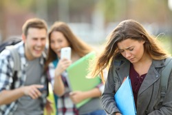 Bullying victim being video recorded on a smartphone by classmates in the street with a unfocused background