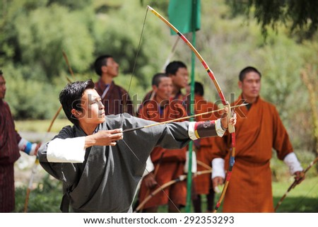 BUMTHANG, BHUTAN - OCTOBER 5, 2010:  A group of Bhutanese men compete in the national sport of archery a festival