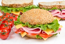 bun and sandwiches with ham, cheese and tomato