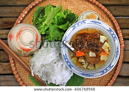 Bun Cha - Vietnamese cuisine: Grilled pork with tasty fish sauce, rice noodles and herbs on a bamboo tray #606768968