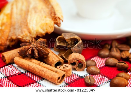 bun, coffee and cinnamon on a red tablecloth