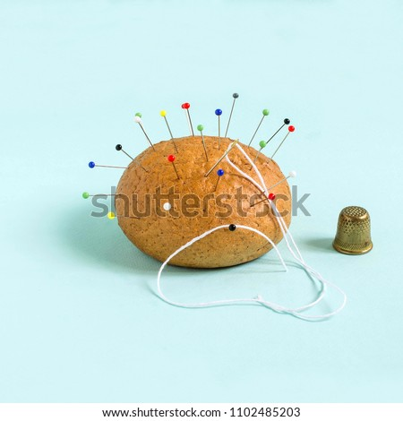 Bun like needle bed and thimble on pastel blue background. Minimalistic style. Creative idea, imagination and fantasy. Food concept. Bringing attention to problems of inactivity and obesity