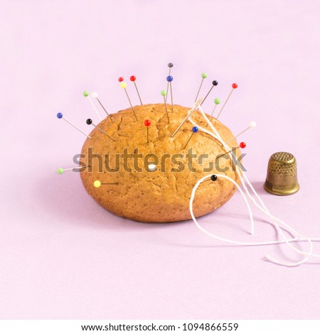 Bun like needle bed and thimble on pastel pink background. Minimalistic style. Creative idea, imagination and fantasy. Food concept. Bringing attention to problems of inactivity and obesity