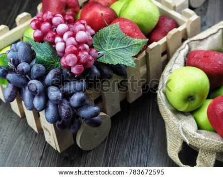 bunch of apples and grapes mixed in decorative basket. selective focus #783672595