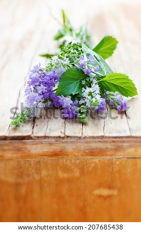 Bunch of aromatic herbs on the vintage wooden cupboard: lavender, mint, thyme, sage