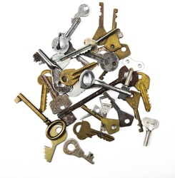 Bunch of assorted old multi-colored metal antique keys of different shapes isolated on white background. Home security concept.